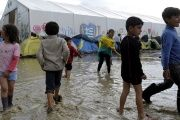 Children play in a puddle following heavy rainfall at a makeshift camp for migrants in Greece.