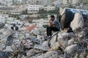 A Palestinian man sits atop the rubble of a house which was destroyed by Israeli troops during an Israeli raid in the West Bank city of Jenin, Sept. 1, 2015.