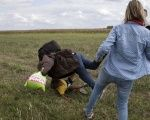 A refugee carrying a child falls after TV camerawoman Petra Laszlo tripped him while trying to escape from a collection point in Roszke village, Hungary, Sept. 8, 2015.