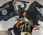 A member of Turkish-backed Free Syrian Army (FSA), seen with a mural of the Islamic State in the background, stands guard in front of a building in the border town of Jarablus, Syria, August 31, 2016.