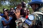 A soldier with the U.N. Stabilization Mission in Haiti gestures to local residents waiting to receive bottled water.