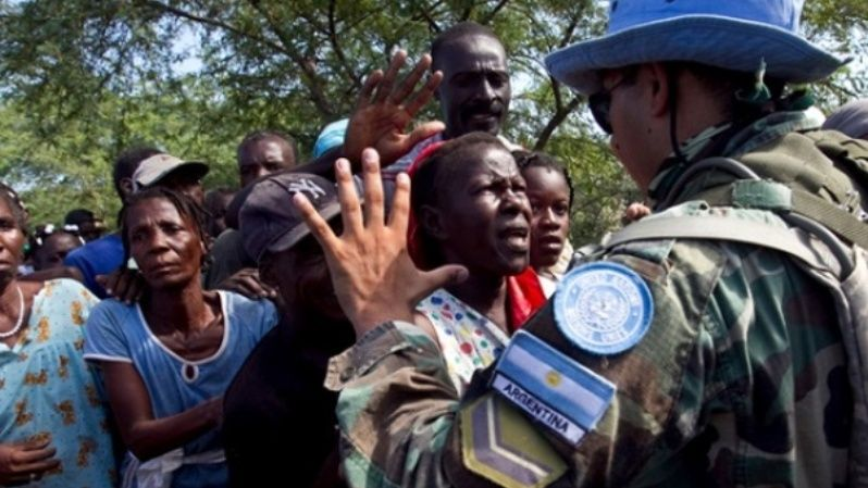 A soldier with the UN Stabilization Mission in Haiti gestures to local residents waiting to receive bottled water.