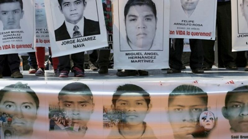 Relatives hold up posters in support of 43 disappeared students from the Ayotzinapa teacher training college during a rally in Mexico City, Feb. 19, 2015.