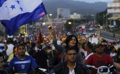 A woman holds a Honduras flag in a march demanding the resignation of President Juan Orlando Hernandez in Tegucigalpa, July 3, 2015.