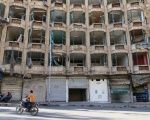 A man rides a motorcycle past a damaged building in the rebel-held al-Shaar neighbourhood of Aleppo, Syria, September 17, 2016.