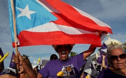 A member of a labor union shouts slogans while holding a Puerto Rico flag during a protest in San Juan, Sept. 11, 2015.
