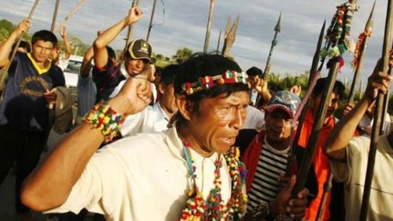 A group of Indigenous people brandish spears while blocking a highway in Peru