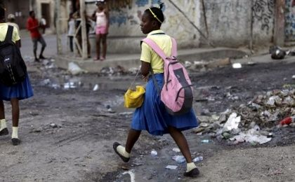 A school girl steps over a puddle in Port-au-Prince, Haiti, January 2016.