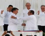 Colombian President Juan Manuel Santos and FARC-EP leader Timoleon Jimenez shake hands after signing the peace accord.