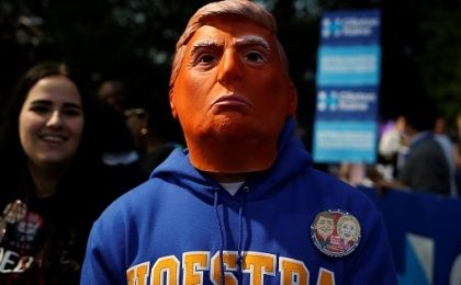 A man stands while wearing a mask depicting Republican nominee Donald Trump outside Hofstra University, Sept. 26, 2016.