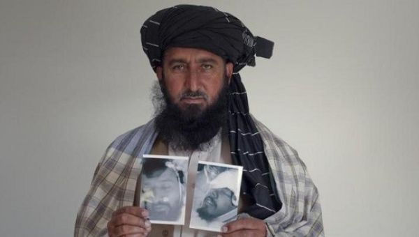 Karim Khan, 43, poses with images of his deceased brother Asif Iqbal (L) and son Zaenullah, Nov. 30, 2010.