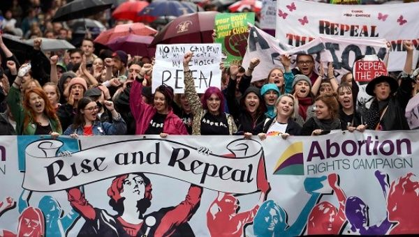 Demonstrators take part in a protest to urge the Irish Government to repeal strict limitations on a woman