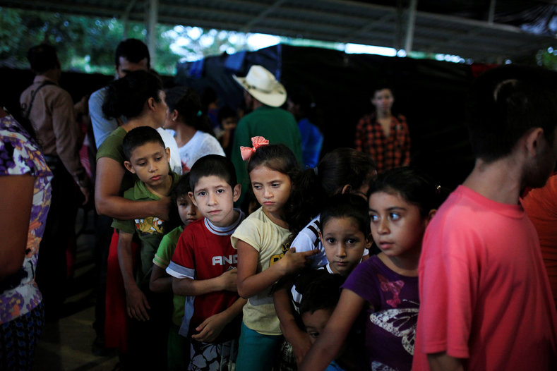 Children queue at dinner time at a shelter for displaced people from El Castano village.