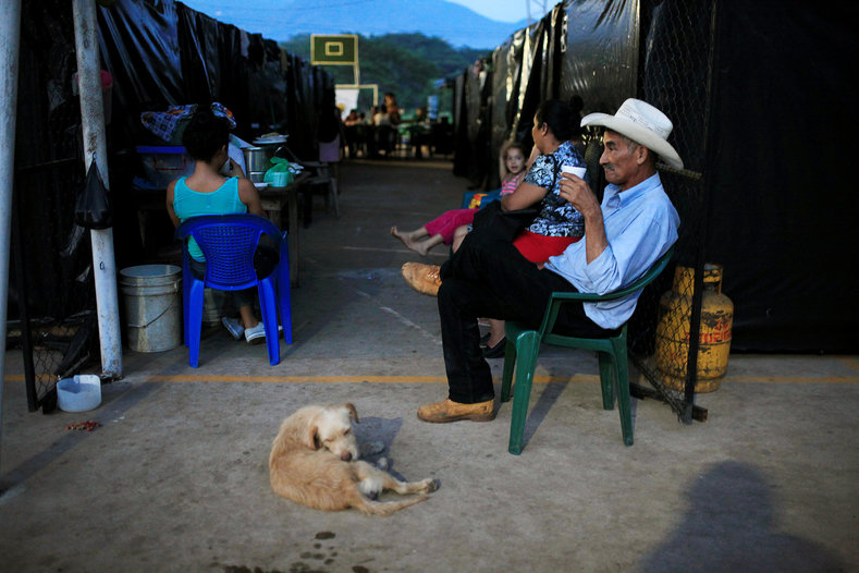 People rest after dinner time at a shelter for displaced people. About 15 families took refuge in a shelter after leaving their homes due to death threats from barrio 18 gang members.