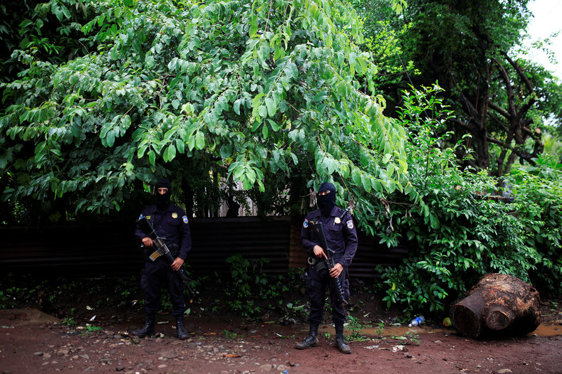 Policemen guard outside a home as residents fled from violent street gang Barrio 18.