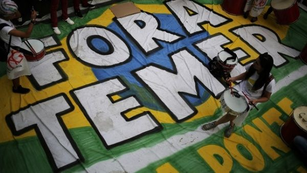 "People from social movements stand on a banner reading ""Out Temer"" during a demonstration against Brazil"