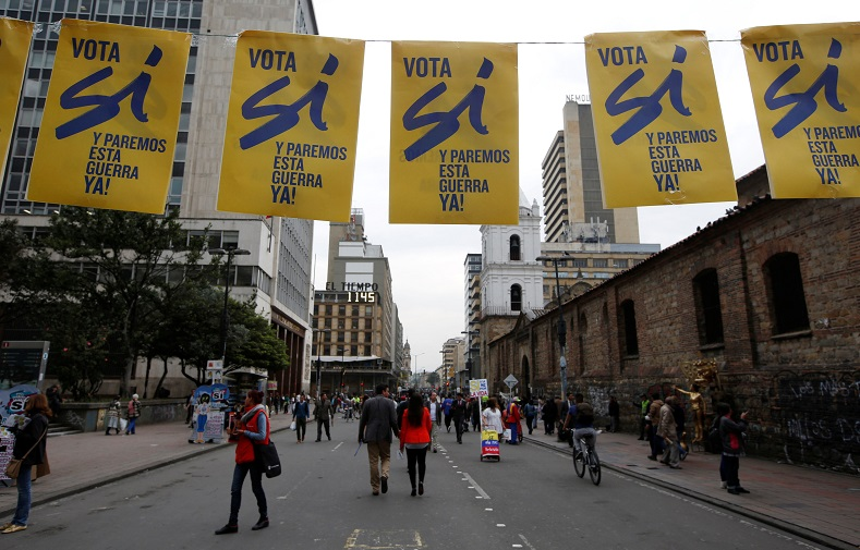 Pedestrians walks under a banner supporting Colombian plebiscite in downtown in Bogota, Colombia, Sept. 29, 2016.