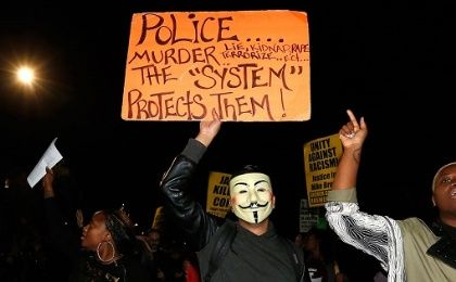 People chant and hold up protest signs during a demonstration in Los Angeles, California.