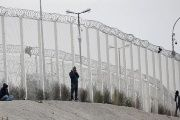 Migrants are seen near the razor-wire topped fence in Calais, France, which secures the road approach to the city and dissuade them from trying to reach Britain on lorries.