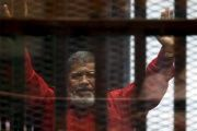 Egypt's deposed president Mohamed Mursi greets his lawyers and people from behind bars at a court wearing the red uniform of a prisoner sentenced to death, during his court appearance with Muslim Brotherhood members on the outskirts of Cairo, Egypt, June 21, 2015.