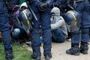 French police stand near as migrants with their belongings queue at the start of their evacuation and transfer to reception centers in France.
