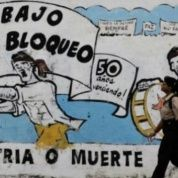 A pedestrian walks past graffiti in Cuba that reads