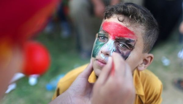 A boy has his face painted with the colors of the Palestinian flag during an event organized by the Palestinian Center For Human Perseverance-Fata in Khan Younis in the southern Gaza Strip Oct. 26, 2016.