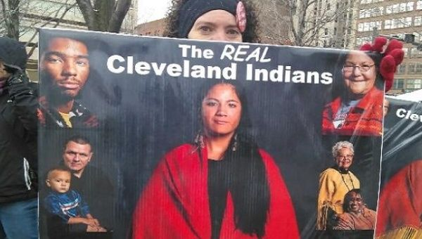 An unidentified protester holds a sign in protest of the Cleveland Indians