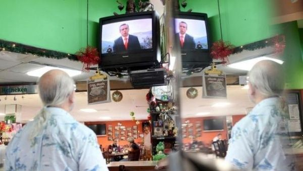 A man watches Puerto Rico Governor Alejandro Garcia Padilla addressing the nation in a televised speech, at a restaurant in San Juan, Dec. 14, 2015.