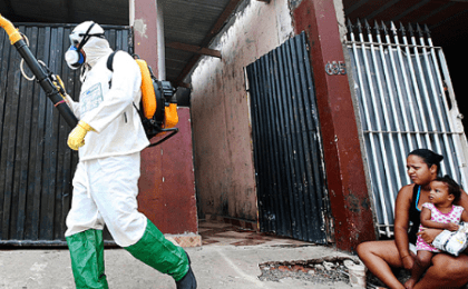 A health official walks past residents as he carries out fumigation to help control the spread of Chikungunya and dengue fever, Mar.6, 2015