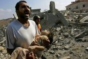 A man carries the body of a young girl killed in an Israeli bomb attack on Qana, South Lebanon, on July 30, 2006.