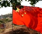 A Chinese flag flutters on the border of China's Yunnan province and Myanmar's Kokang region in Nansan, March 7, 2015.