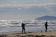 Workers clean a beach on the coast of Rimini, Italy, April 16, 2014.