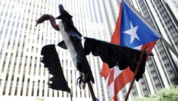 A vulture puppet is held at a protest against Puerto Rico