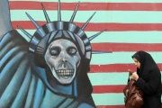 An Iranian woman walks past an anti-US mural painted on the wall of the former U.S. embassy in Tehran.