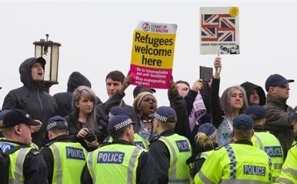 Anti-racism demonstrators hold up placards and chant slogans as a far-right group marches through Dover, southern England, on April 2, 2016.