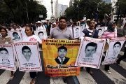 Relatives carry photos of the 43 missing students of the Ayotzinapa teachers' college during a protest in Mexico City, Aug. 26, 2015.