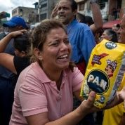 A distraught woman holds up a bag of Pan cornflour, a staple of the Venezuelan diet made by the Polar Company, Caracas, Venezuela, June 11, 2016.