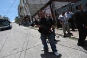 A police officer stands guard after a shooting  in Guatemala City, July 8, 2013.