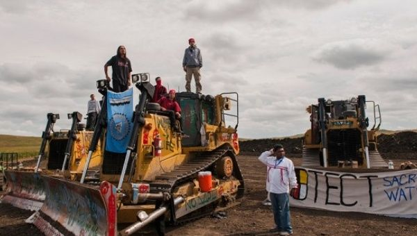 Protesters stand on machinery after halting work on the Dakota Access pipeline near the Standing Rock Sioux reservation, North Dakota, Sept. 6, 2016.
