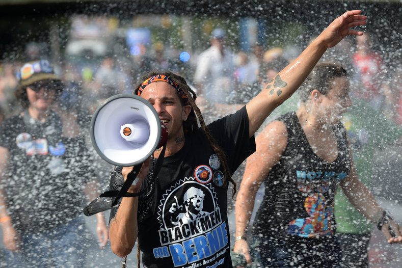 "A white male with dreadlocks wearing a ""Black Men for Bernie"" t-shirt reacts to a jet of water."