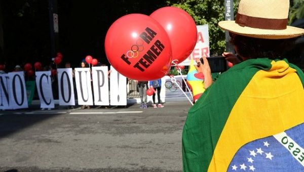 "A demonstrator wearing a Brazilian flag carries a balloon reading ""Temer, out"" against a sign saying ""No coup!"" in Sao Paulo"