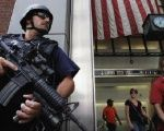 Members of the public react as they walk past an NYPD Hercules team on patrol near Penn Station in New York City.