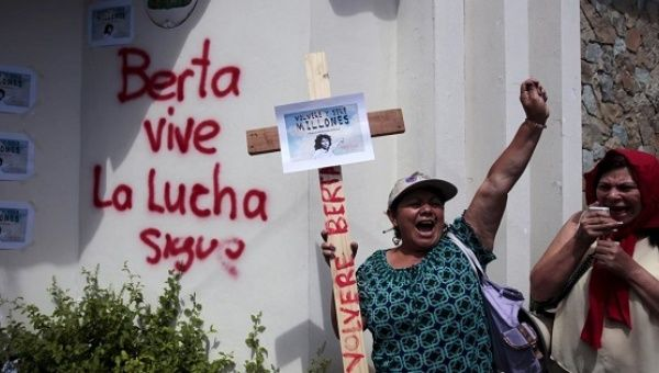 "Women protest the killing the Berta Caceres next to graffiti that reads ""Berta lives, the fight continues."""