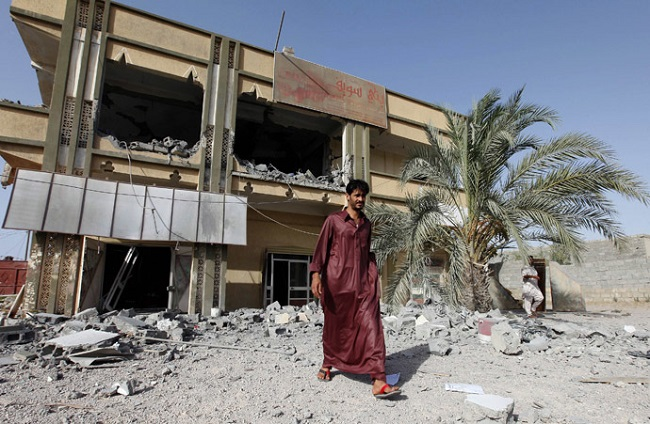A man walks past the premises of a transport company which the Libyan government said was destroyed by NATO air strikes in Zliten, about 150km (93.2 miles) east of Tripoli July 21, 2011.