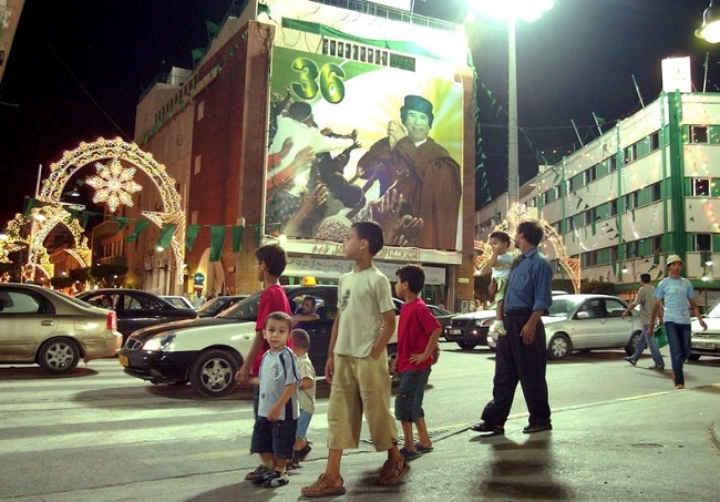 Aug 2005: Children walk past a poster of Libyan leader Moammar Gadhafi, as Libya prepares to celebrate the 36th anniversary of the Libyan Revolution, which overthrew the monarchy in Tripoli.