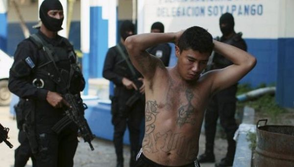 One of 13 suspected members of the 18th street gang is arrested by the police under the charges of homicide and terrorism, in Soyapango, El Salvador March 31, 2016.