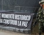 "A Colombian soldier stands at an army checkpoint next to a sign saying ""This is a historic moment to build peace"