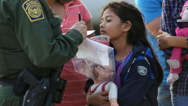 A young undocumented Salvadorean immigrant watches as a U.S. Border Patrol agent records family information.