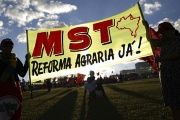 MST activists hold a sign in Brasilia demanding